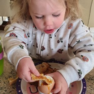 2 year old enjoying dipping eggs on Easter Morning